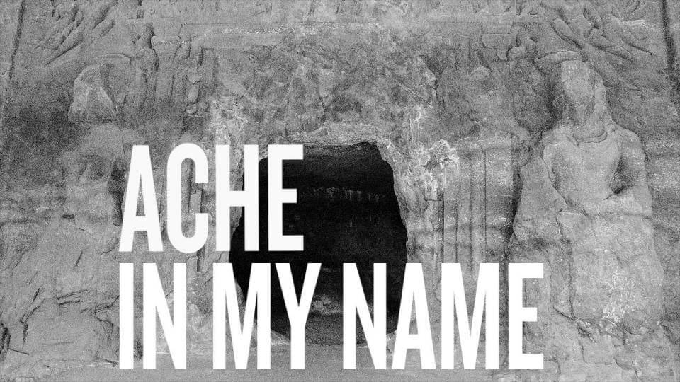 Pale grey rock, the heavily-eroded entrance to a temple, with a dark black opening. Overlaid in bold white text are the words 'Ache In My Name'.