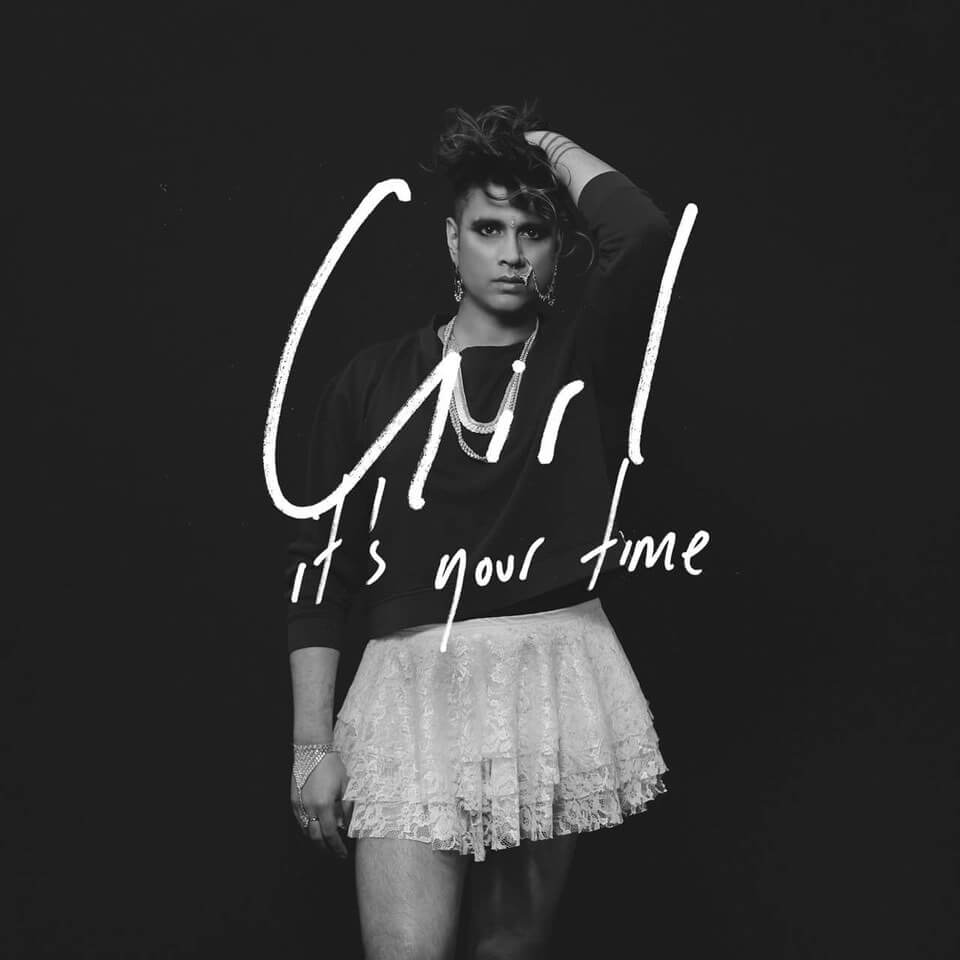"A B&W photo of a brown-skinned femme in her mid-30s standing in front of a black background wearing a plain black sweatshirt and lacy white skirt, overlaid with white handwritten text, ""Girl It's Your Time""."