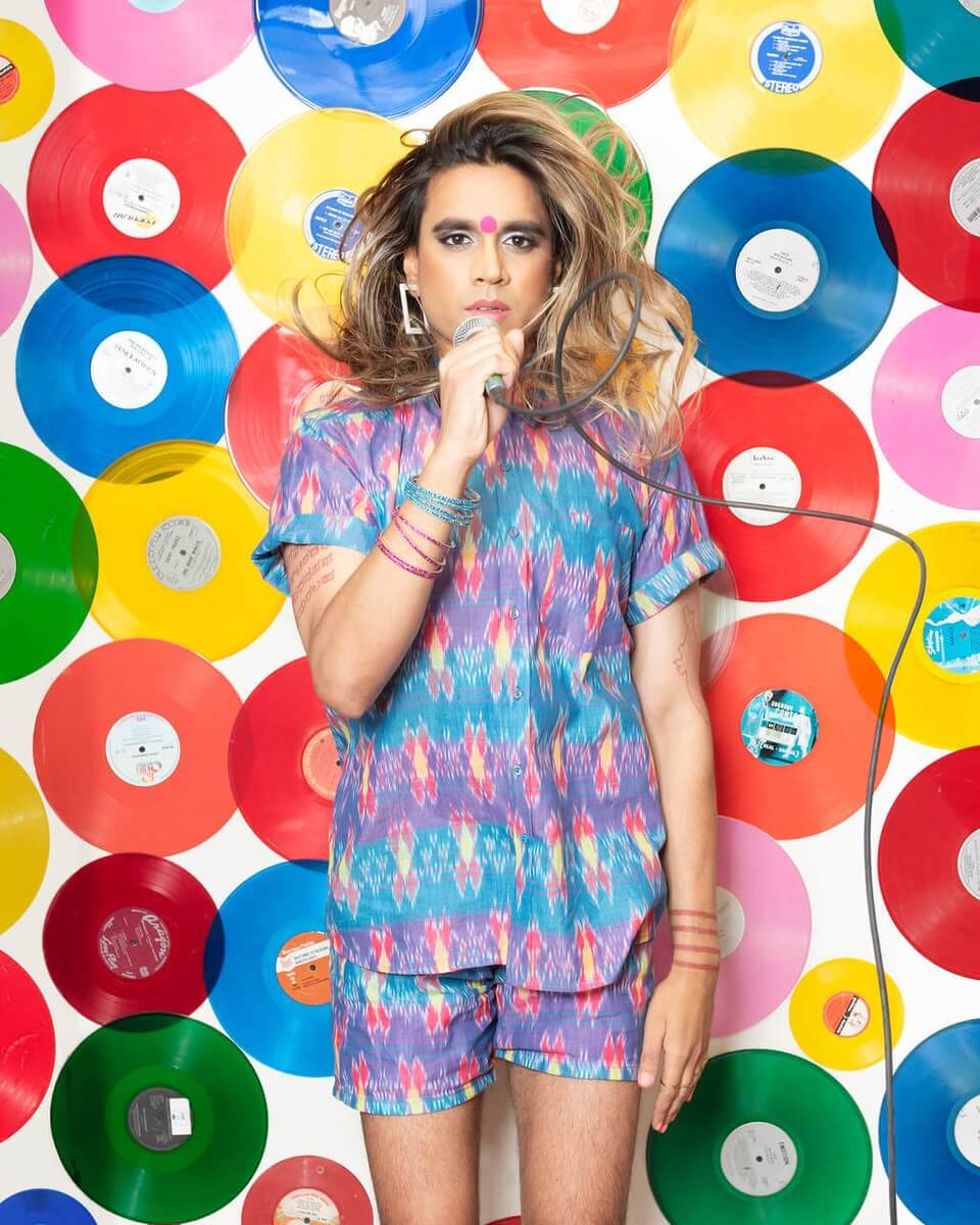 A brown-skinned trans woman with blonde-streaked hair and a red bindi, holding a microphone and standing in front of a wall covered in colourful vinyl records.