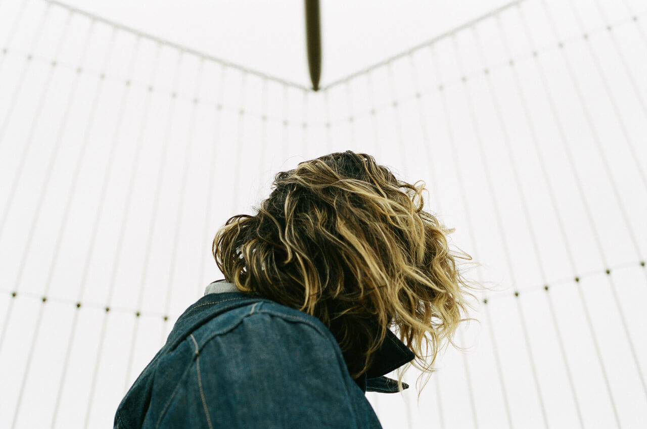 A head-and-shoulders photo of a woman in a denim jacket standing on a bridge in front of an anti-suicide fence. Her face is turned away and obscured by her upturned collar and blonde-streaked black hair.