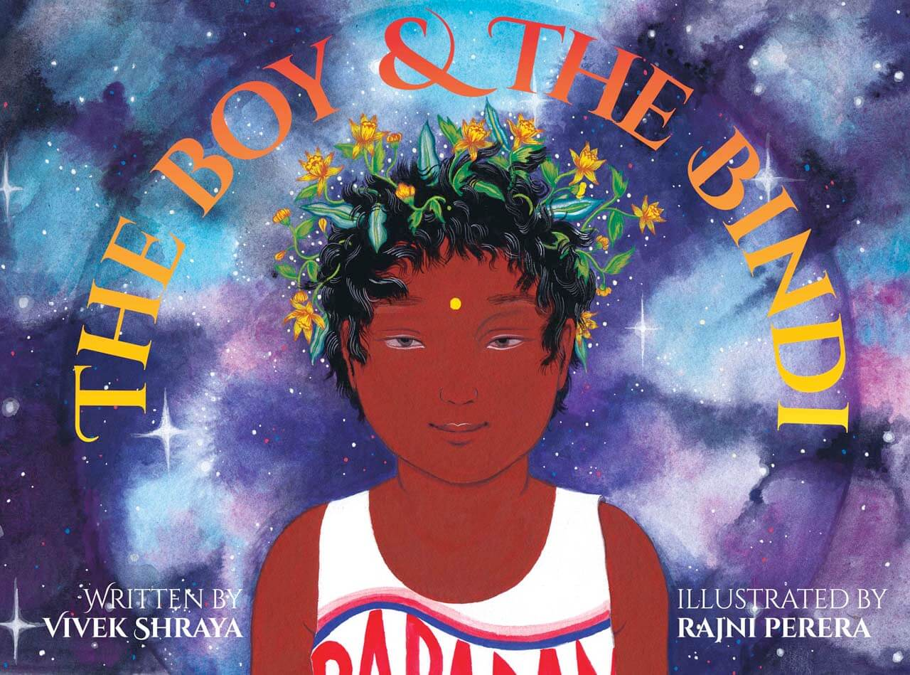 An illustration of a young, smiling, brown-skinned boy with flowers in his hair, against a colourful starry background. Text: The Boy & The Bindi; Written by Vivek Shraya; Illustrated by Rajni Perera.