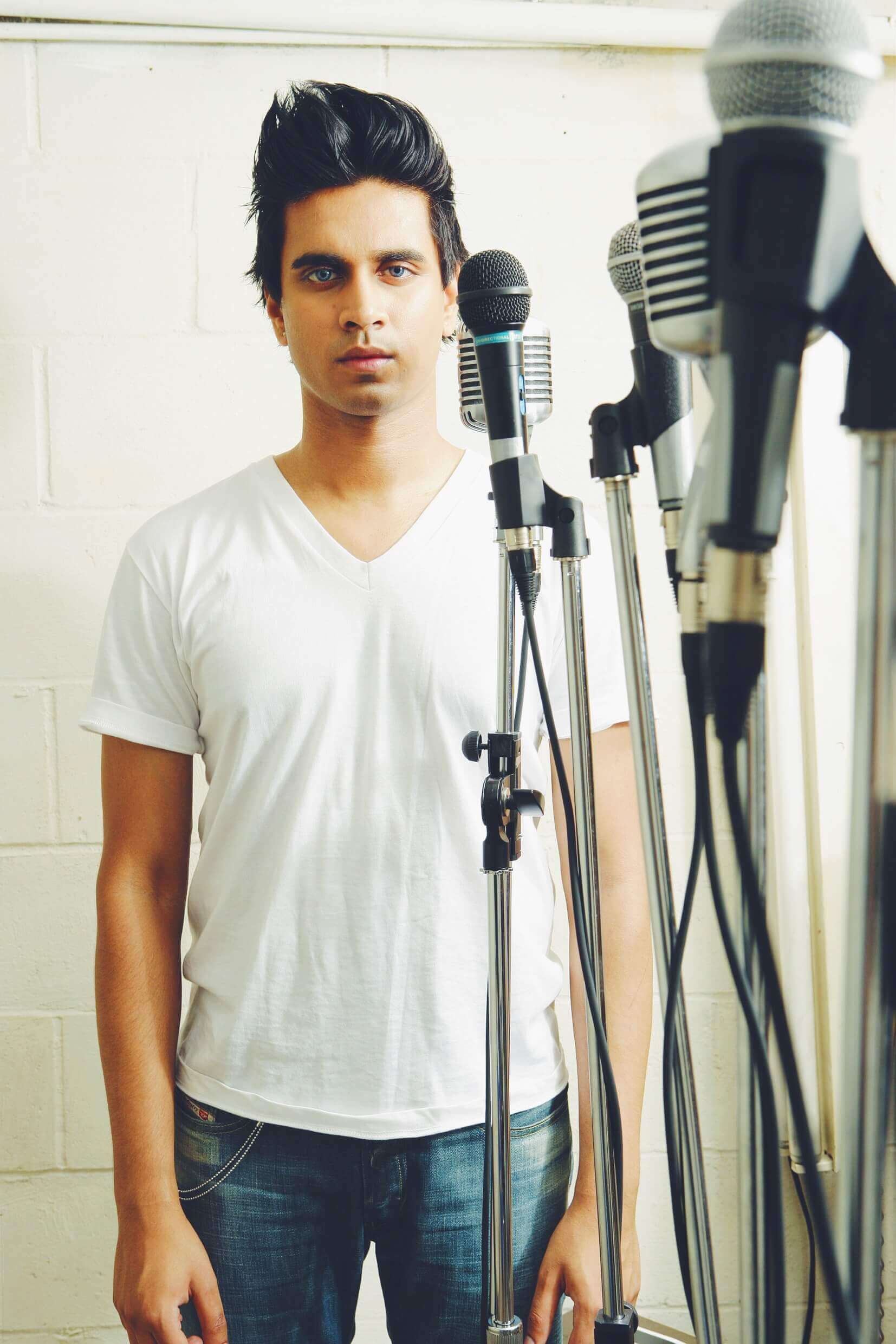Vivek stands in front of a white cinderblock wall wearing a white v-neck t-shirt and blue jeans. Several microphones stand between her and the camera.